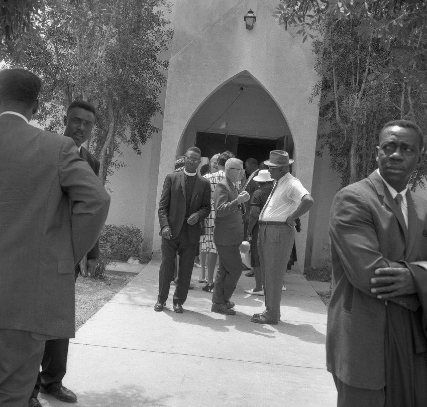 Historic photo of men standing on sidewalk in front of unidentified building