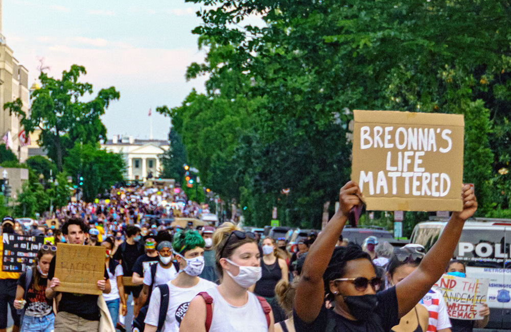 Protestors marching in Washington DC with signs, including one that says Breonna's Life Mattered