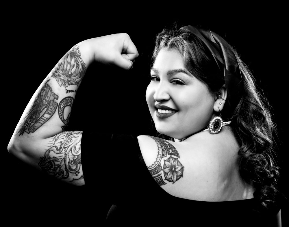 Black and white photo of Corinne Zepeda showing off her tattoos in a Rosie The Riveter pose