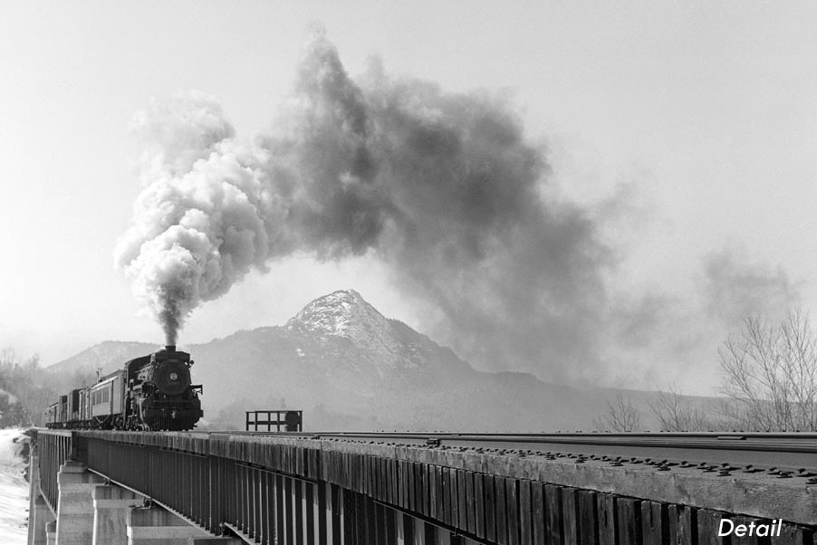 Black and white photo of steam engine crossing a trestle in front of mountain