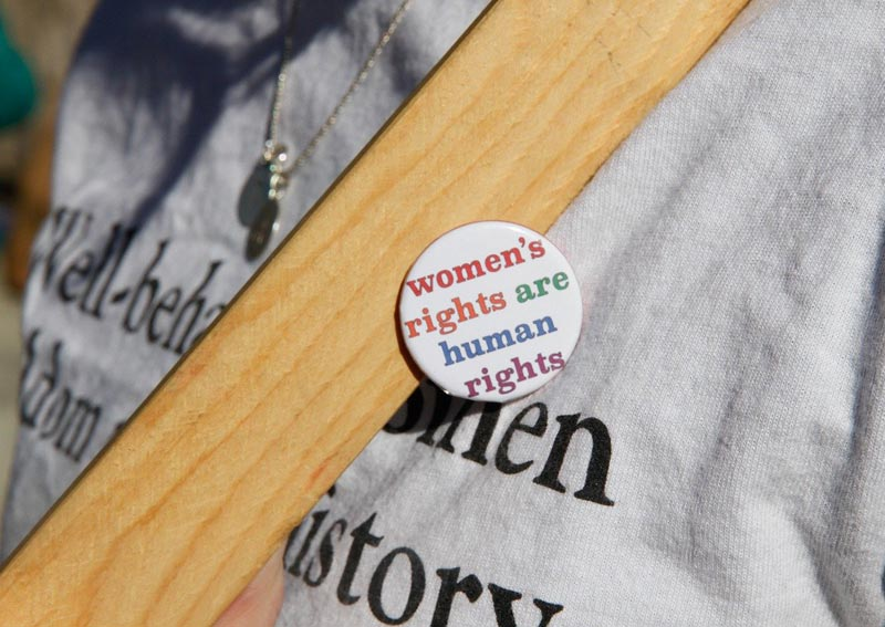 Close-up photo of protestor with button that says women's rights are human rights