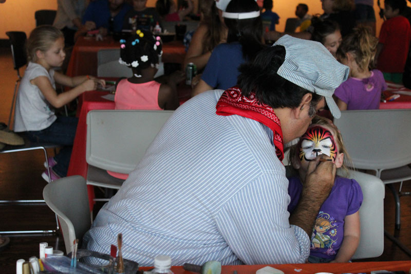 Photo of man in train engineer costume at face-painting booth