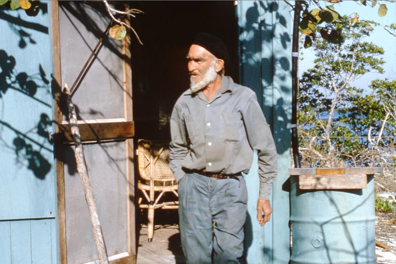 Photo of Roy Ozmer in front of a blue shed