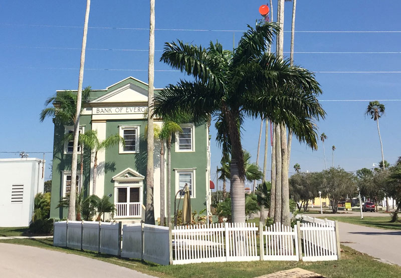 Photo of the Bank of the Everglades, a green neoclassical building with a palm tree in front