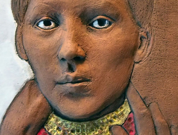 Detail of portrait sculpture by Jessica Osceola showing terracotta colored face with yellow collar at neck