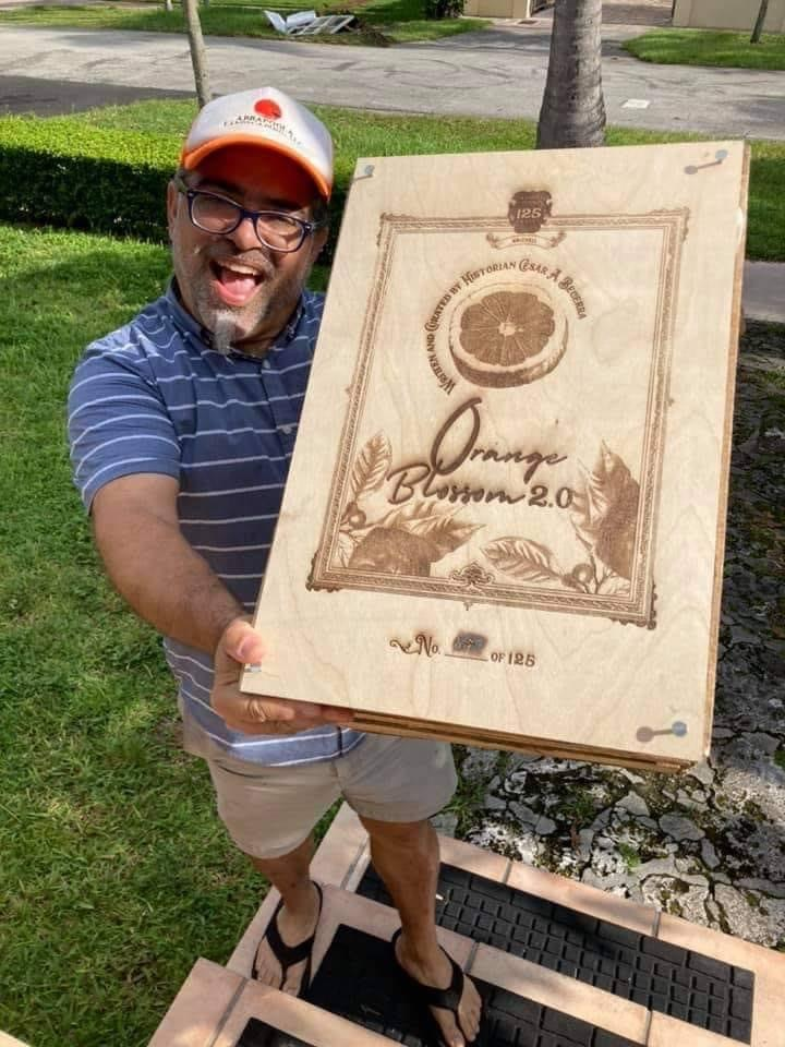 Photo of Cesar Becerra holding a large wooden replica of his Orange Blossom 2.0 book