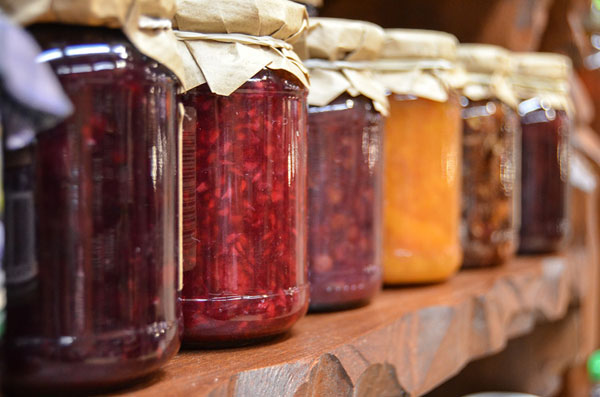 Photo of row of jars with canned fruits inside